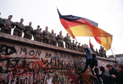German freedom fighters try to climb onto the Berlin Wall as East Berlin border guards prevent the  crowd from crossing, Nov. 10, 1989. Photo via Tom Stoddart of Getty Images.